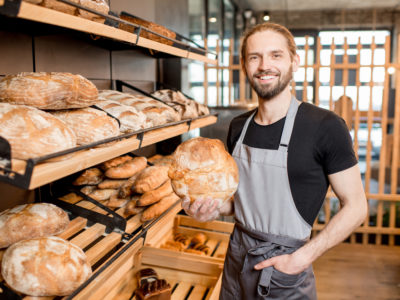 Portrait of a handsome seller in uniform standing with bread at the bakery shop